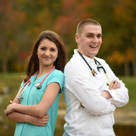 Fiance with husband to be standing shoulder to shoulder with stethoscopes smiling at the camera