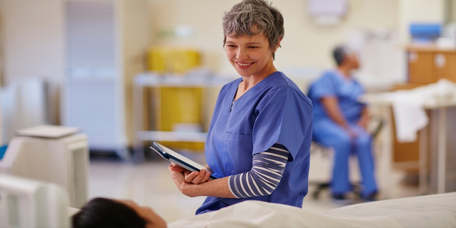 Female nurse in scrubs smiling and talking to patient on hospital bed