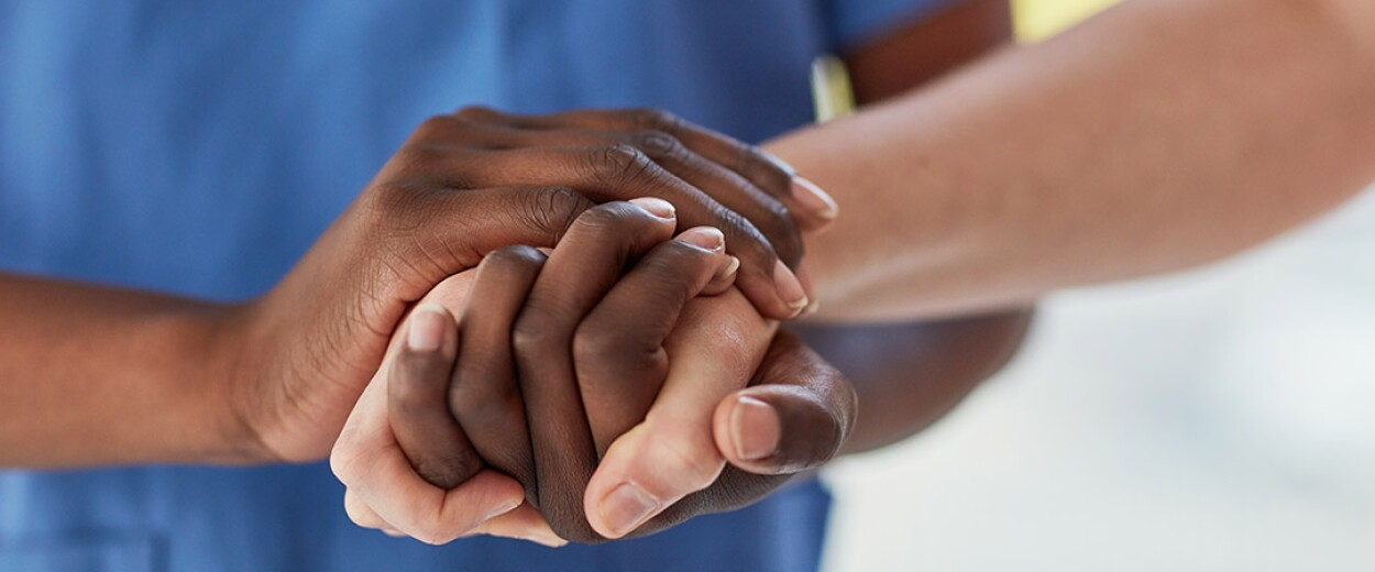 Image of two sets of hand clasped together