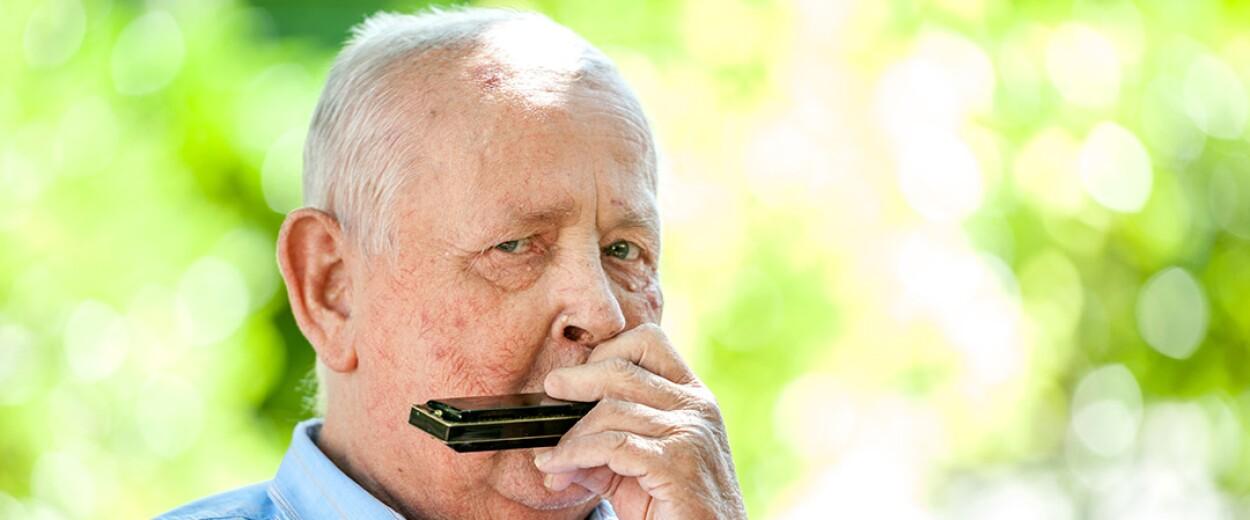 Elderly man playing harmonica
