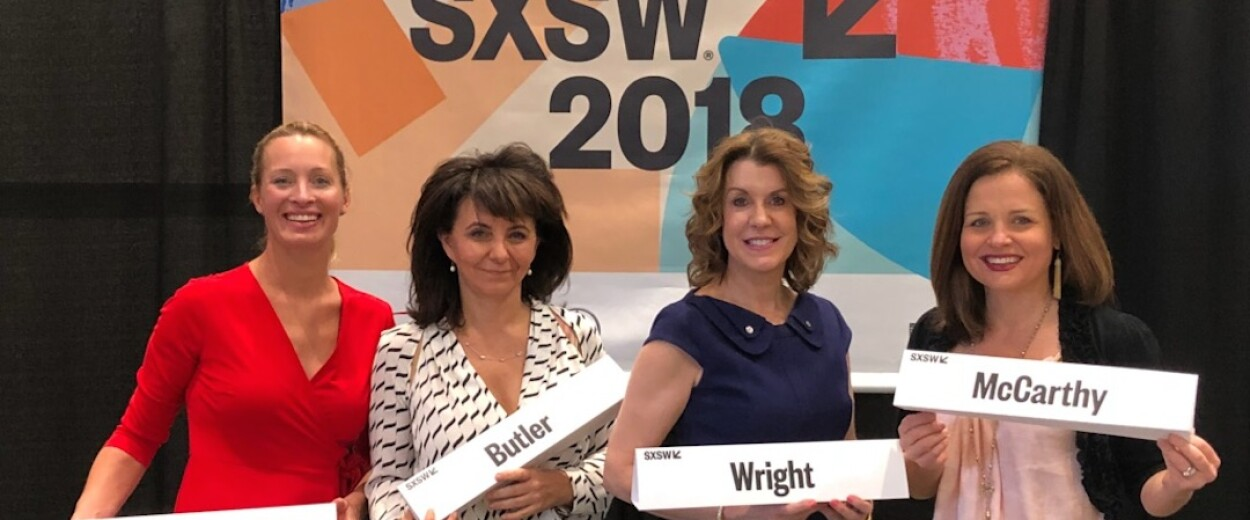 Four women holding their name cards in front of the SXSW 2018 banner