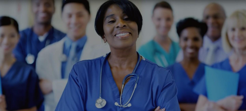 Group of smiling nurses in scrubs holding folders