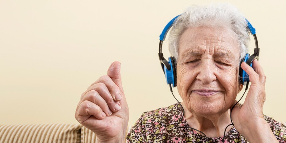Elderly woman listening to something on blue headphones