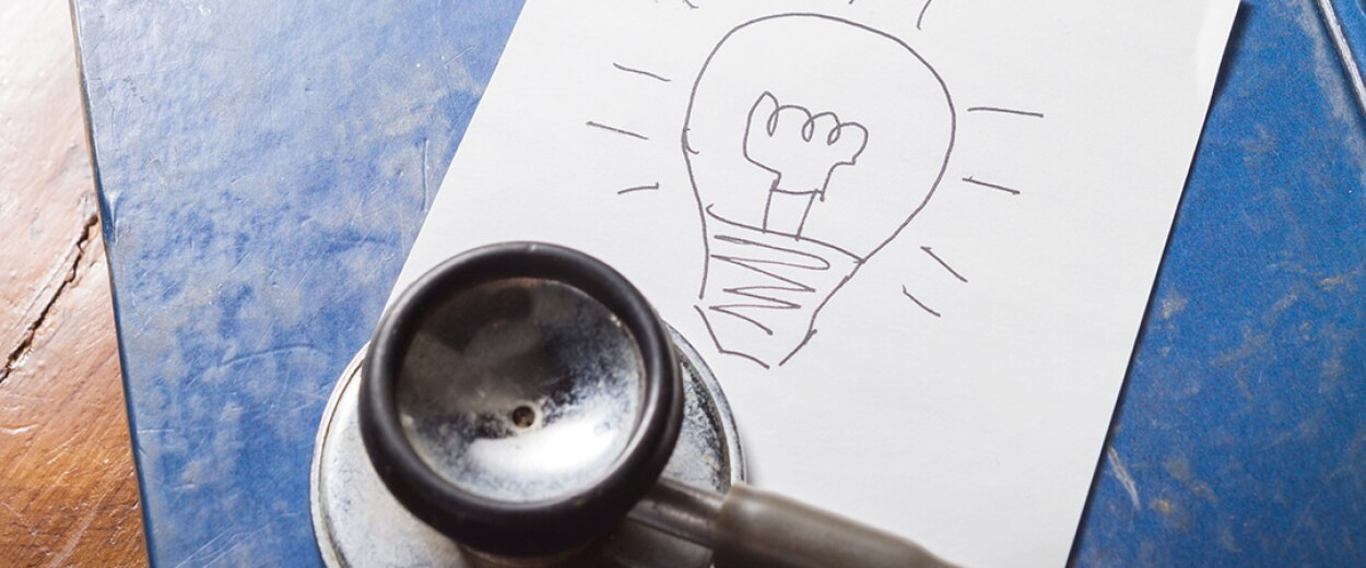 A stethoscope resting next to a piece of paper with a lightbulb drawn on it