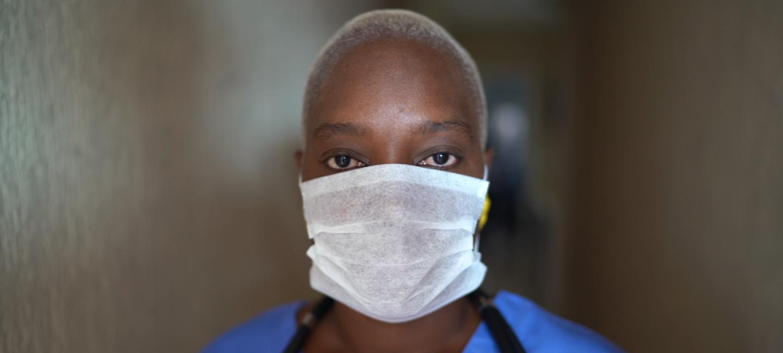 Female nurse in scrubs wearing face mask looking at camera