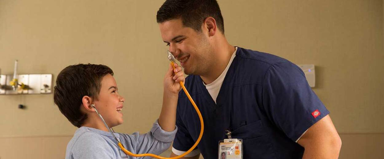 Male nurse in scrubs letting male child patient play with stethoscope