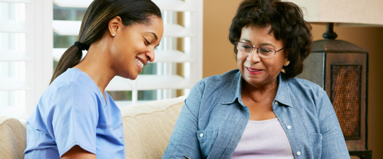 Smiling female nurse and female patient sitting on couch reviewing information on paper