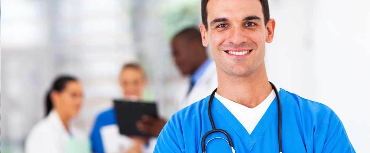 Male nurse in scrubs smiling at camera