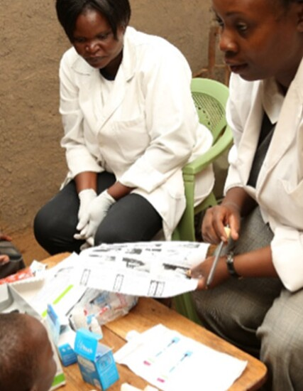 Two female nurses in lab coats explaining information to a mother and her two children