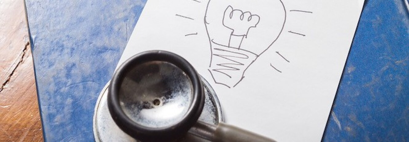 Stethoscope next to piece of paper with lightbulb drawn on it