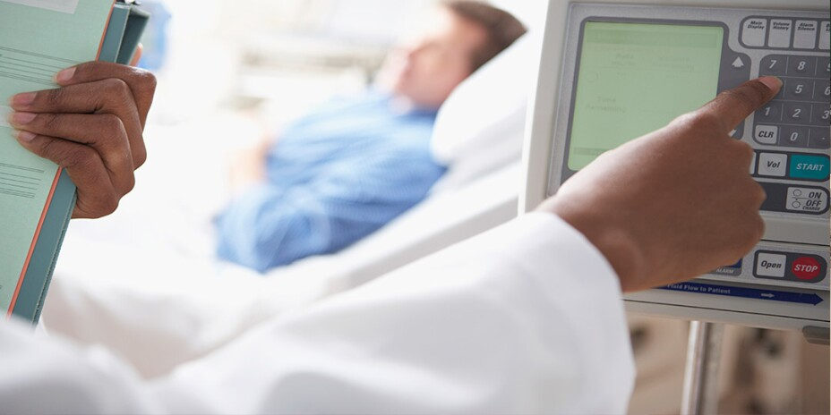 Close up of medical personnel typing numbers in on a monitor with a male patient in hospital bed in background