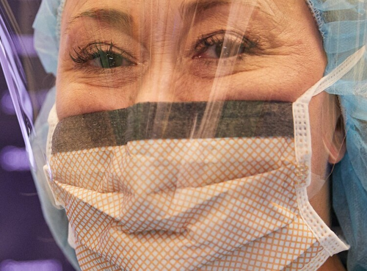 Close-up of a female nurse in scrubs, face mask, and face shield