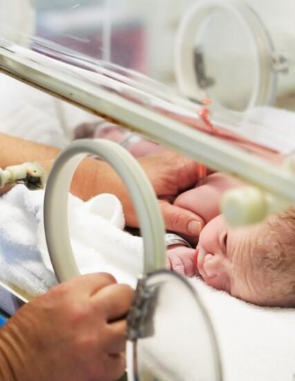 Female nurse comforting newborn baby laying in clear bassinet in NICU setting