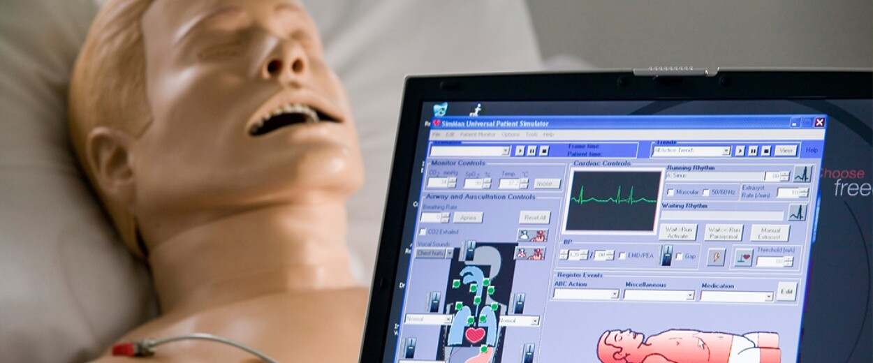 Demonstration of medical dummy in hospital bed with a tablet of his vitals