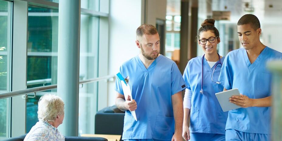 Three nurses in scrubs looking at a tablet walking down a hospital corridor