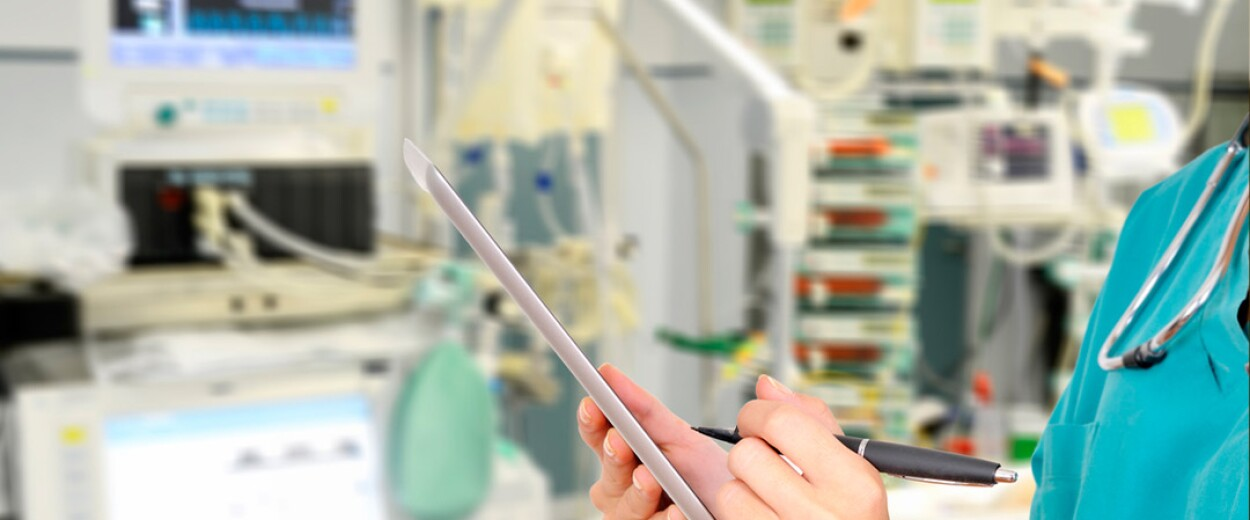 Close up of medical personnel writing on a tablet in a hospital setting