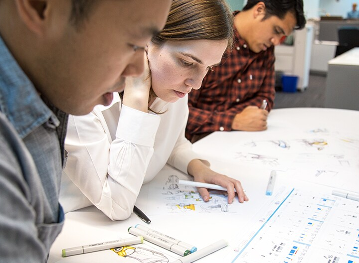 Three students studying over bio mechanical blueprints
