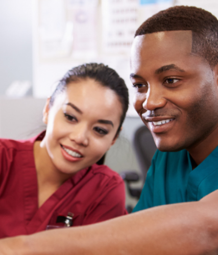 Male and female nurse in scrubs smiling while looking at computer