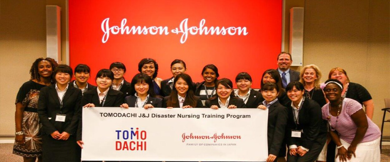 A large group of woman and a man holding a TOMODACHI J&J Disaster Nursing Training Program banner