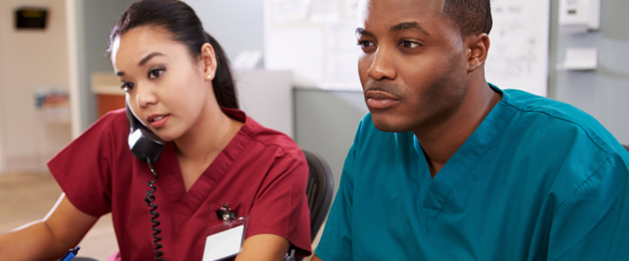 Male and female nurse in scrubs looking at computer screen while female nurse talks on phone